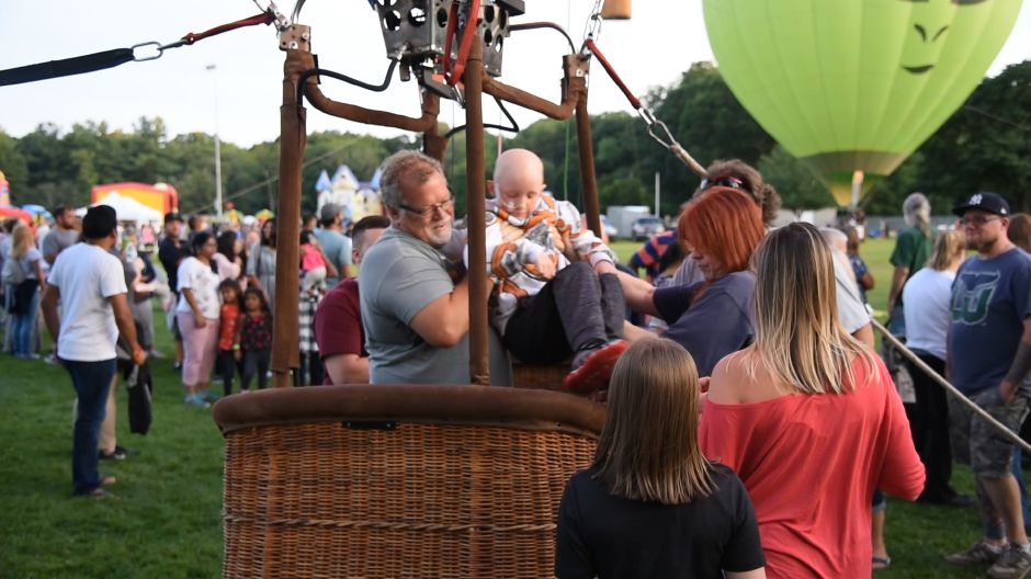 Plainville resident Axel Sundberg, 10, left, gets some help getting into a hot air balloon basket for a ride during the first night of this year