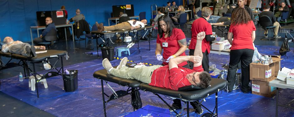 Teresa Padilla, Red Cross collections staff, assists donor Christopher Geist, of Wallingford, during a blood drive on Tuesday at the State Police Academy in Meriden. Dave Zajac, Record-Journal