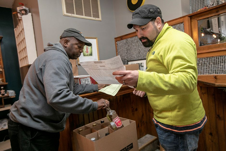 Jared Andrew Brown, right, co-founder and artistic director of The Square Foot Theatre, looks over a a list of liquor delivered by William Watson, left, a driver for Hartley and Parker Limited, Inc., Tues., Apr. 2, 2019. The theatre is opening a bar and lounge. Dave Zajac, Record-Journal