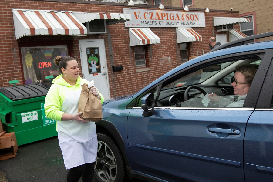 Helper Jess Skiffington, left, brings longtime customer Gina Quinn her Easter kielbasa at V. Czapiga & Son on Cooper Street in Meriden on Friday.