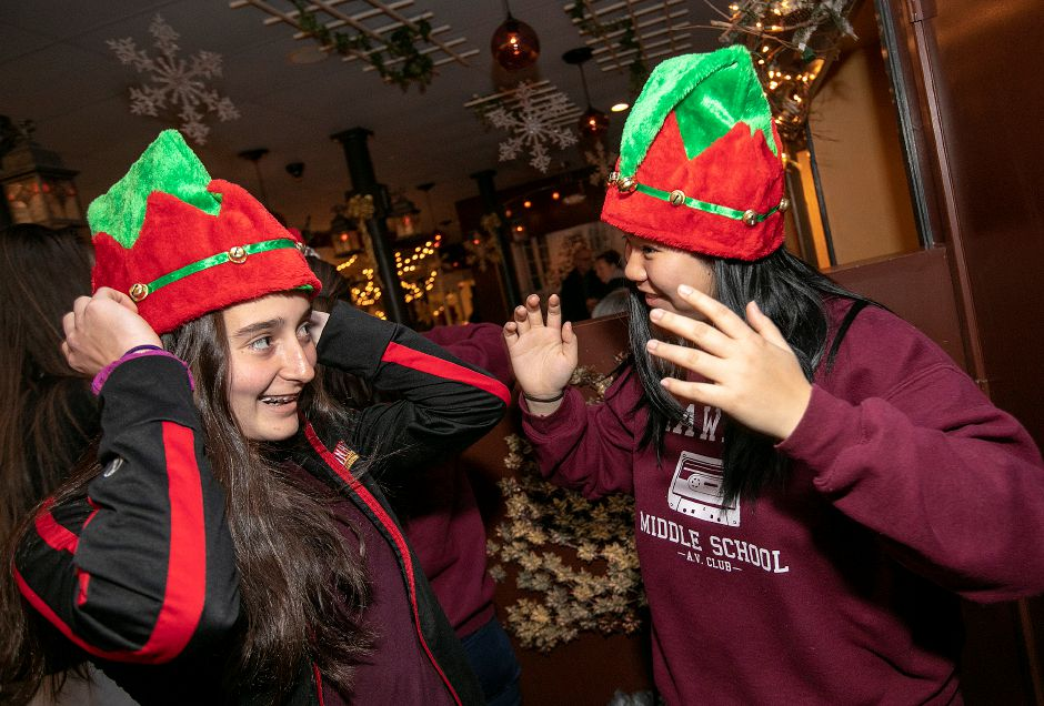 Lyman Hall High School volunteers Emily Chase, 14, left, and Makayla Cao, 14, wear holiday hats during the annual Toys for Tots donation event at Gaetano's Tavern on Main, 40 N. Main St. in Wallingford, Thurs., Dec. 13, 2018. Dave Zajac, Record-Journal