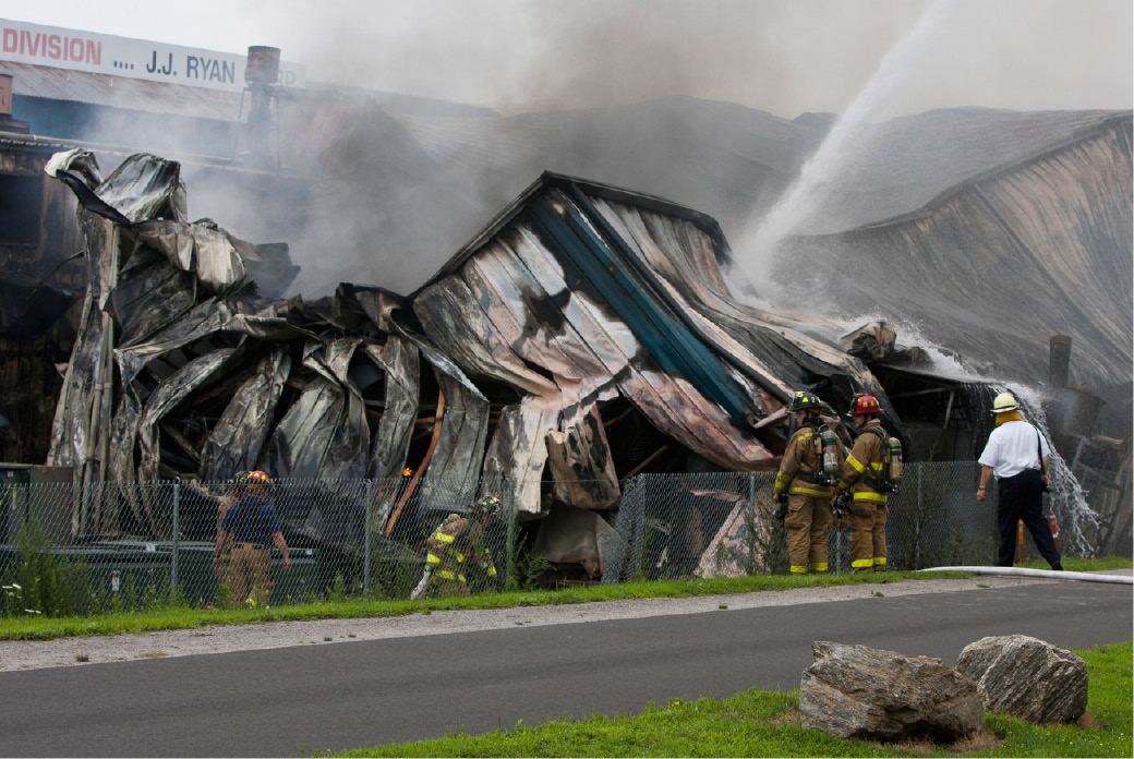 FILE PHOTO: Firefighters get a little closer to survey the damage and find the remain pockets of fire after most of the blaze was knocked down Tuesday morning at the Rex Forge factory on Atwater Street in Southington, July 31, 2012. The intense heat of the fire caused the steel structure to melt and collapse in on itself making the fire more difficult to fight. (Christopher Zajac / Record-Journal)