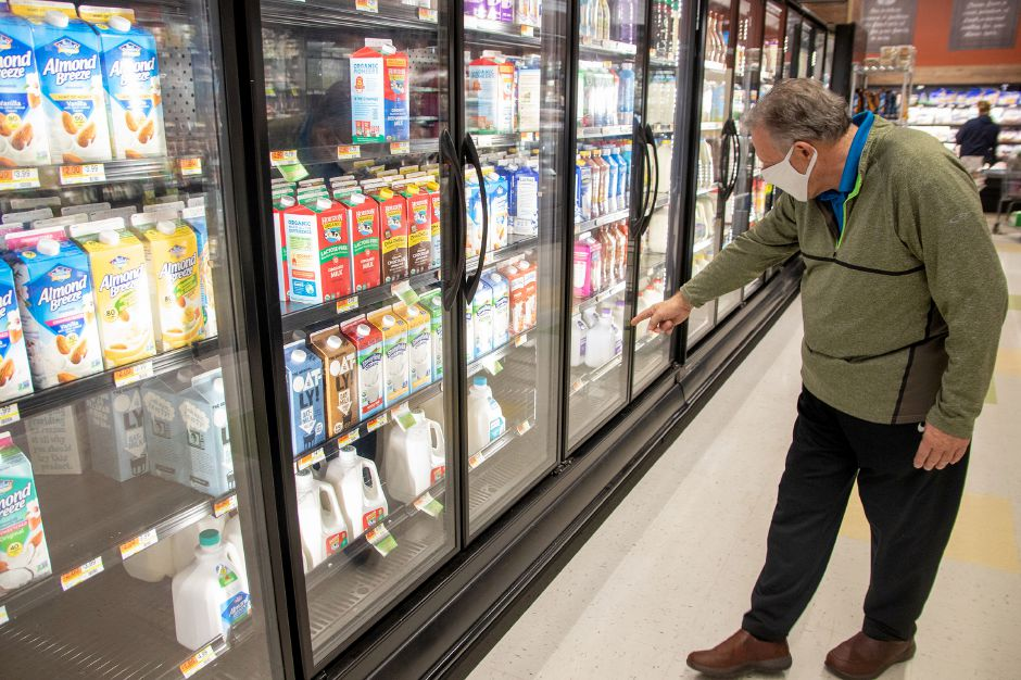 John Salerno, owner of Tops Marketplace in Southington, points to the limited supply of organic milk the store has in stock on Tuesday. Photos by Aaron Flaum, Record-Journal
