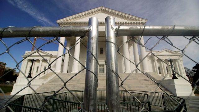 The Virginia state Capitol building is surrounded by fencing, Thursday, Jan. 16, 2020 in Richmond, Va., in preparation for Monday