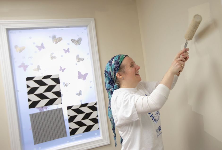 Mirion Technologies employee Jess Lawson paints an office wall while volunteering Tuesday.