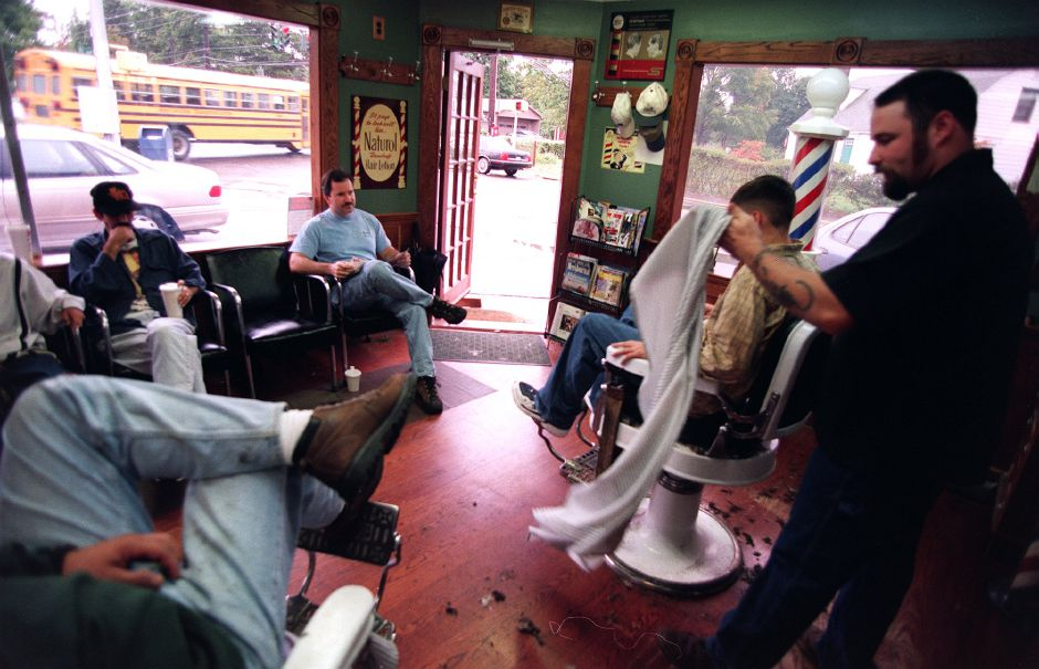 Glenn Agnew, right, finishes a haircut in The Village Barber on Main Street in South Meriden,Oct. 1999. The barbershop is a popular socializing place in the village.