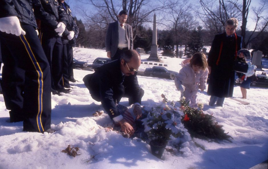 RJ file photo - Meriden Police Det. Sgt. Keith McCurdy arranges flowers on the grave of David Paul , followed by Ann Javornisky, 4, Jan. 2, 1990.