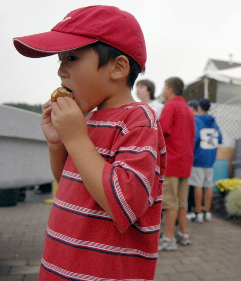 SOUTHINGTON, Connecticut - Saturday, September 27, 2008 - Daniel Yu, 6, of Southington, eats a cinnamon sugar covered hot apple fritter at the 2008 Apple Harvest Festival in downtown Southington on Saturday. Rob Beecher / Record-Journal