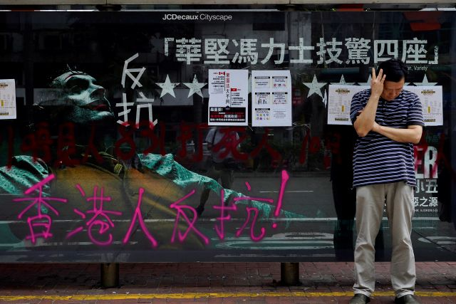 "A man waits for a bus next to graffiti on a commercial display that reads, ""Hong Kong people will fight"" in Hong Kong, Monday, Oct. 7, 2019. Tens of thousands of masked protesters marched defiantly in the city center Sunday, but the peaceful rallies quickly degenerated into chaos at several locations as hard-liners again lobbed gasoline bombs, started fires and trashed subway stations and China-linked banks and shops. (AP Photo/Vincent Yu)"