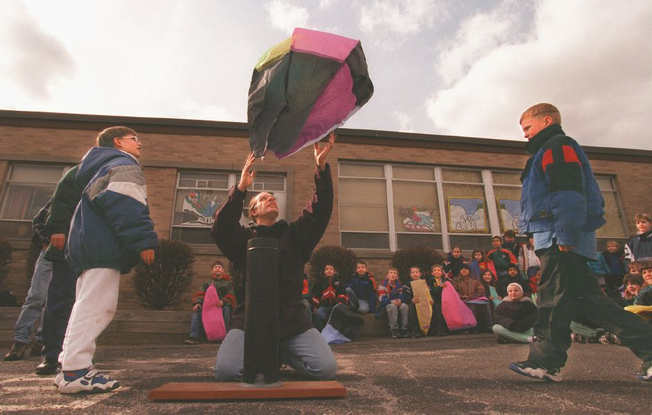 RJ file photo - Mallory Bagwell, center, uses a propane stove to launch a balloon assembled by fourth-graders Christopher Bushnell, left, and Shawn Belden, right, at North Center School in Southington March 13, 1998.