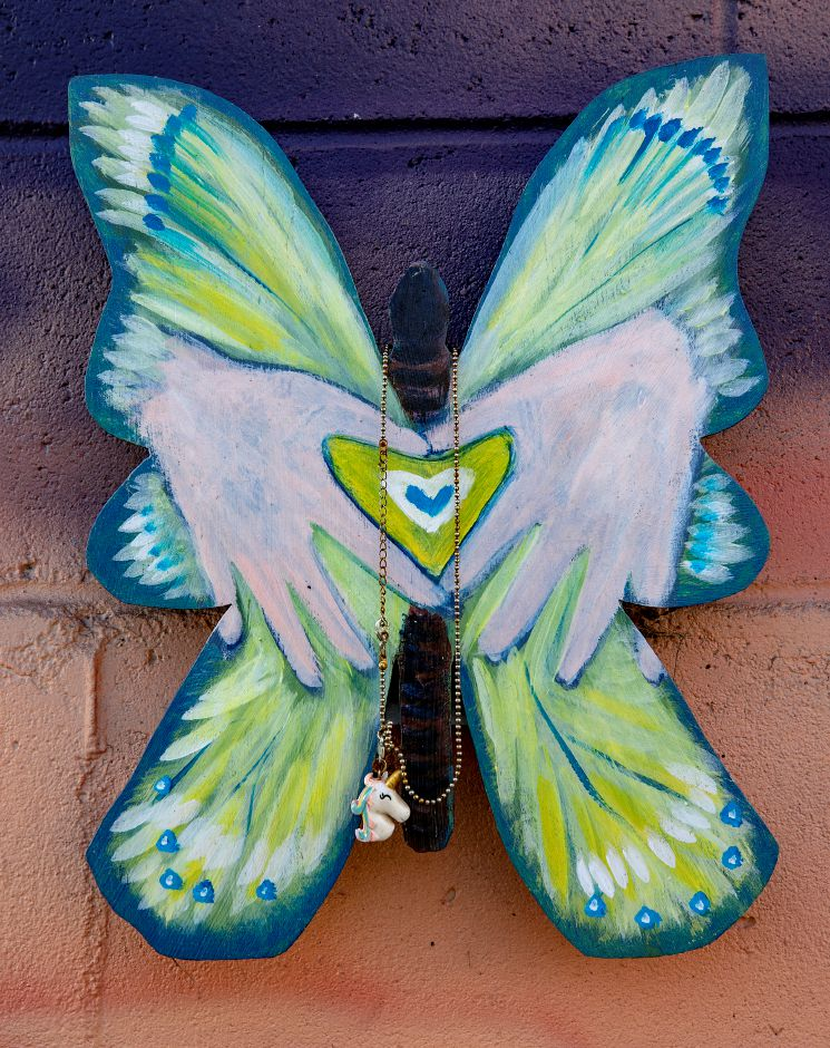 A necklace with unicorn pendant hangs on one of 26 artistic butterflies created for the Sandy Hook mural dedicated to the 26 victims of the Sandy Hook shootings along the Farmington Canal Heritage Trail in Southington, Mon., Dec. 7, 2020. Dave Zajac, Record-Journal
