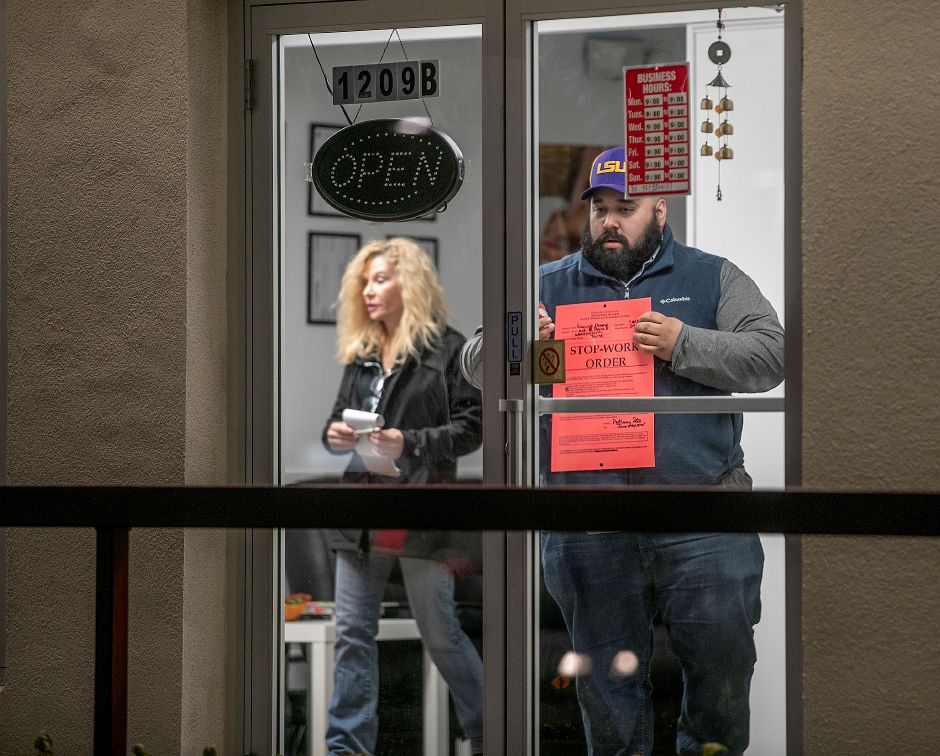 Investigators from the state  Department of Labor  close down Exquisite Massage  at 1209B South Broad St. in Wallingford on Jan. 30.Dave Zajac, Record-Journal