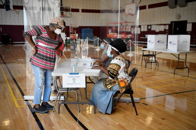 Christine Shannon, left, checks in to vote with volunteer Patricia Nelson, right, at Rawson Elementary School, Tuesday, Aug. 11, 2020, in Hartford, Conn. (AP Photo/Jessica Hill)