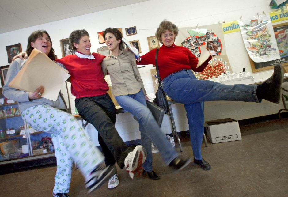 Left to right, teachers Cathy Benedetto, Macia (cq) Phelps , Angela McMinn, and Judy Grimaldi dance in the halls at the conclusion of the school day at North Center School in Southington Friday afternoon February 13, 2004. The teachers were in great spirits for the start of their week long vacation.