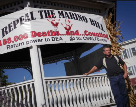 Coalition for a Better Wallingford founder Ken Welch stands in front of a banner he hung on a gazebo at Johanna Manfreda Fishbein Park in Wallingford on Oct. 10, 2017. The banner protests a bill passed through Congress in April 2016 that weakens the Drug Enforcement Administration