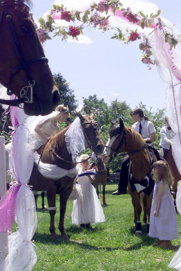 Mary Gace a 10 year old Quarter Horse and Smokey a 23 year old Quarter Horse and part Arab Chesnut, are presented with horeshoes after saying thier vows Sunday afternoon at the Rap-A-Pony Farm in Wallingford June 4, 2000. Peek-A-Boo, one of the two clergy members for the ceremony looks on as the ceremony comes to a close.