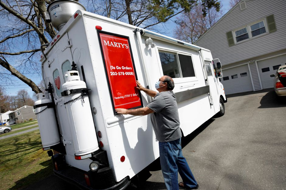 Marty DiVito aligns a sign on his new food truck at his residence in  Wolcott on Friday. DiVito is preparing for a seasonal spot at 2156 Meriden-Waterbury Turnpike where he'll offer steak sandwiches, hamburgers, salads and his own relish. Photos by Dave Zajac, Record-Journal