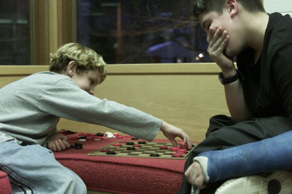 Mike Dudley, 10, makes a move during a game of checkers against Casey Piper, 12, at the Wallingford Library on Wednesday evening Jan. 17, 2001. Piper won the game.
