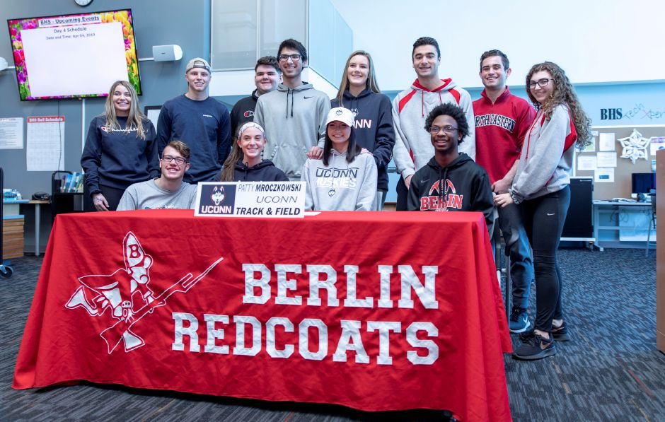 Patty Mroczkowski, center in gray, was one of three Berlin High School athletes who a signed letter during an April 4, 2019 ceremony to play sport at the collegiate level. Mroczkowski will be part of the University of Connecticut's track and field team. | Devin Leith-Yessian/Berlin Citizen