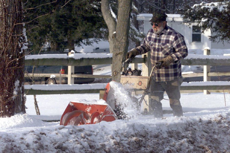 Jerry Bernier, of Southington, clears snow off of the sidewalk around a cemetary in Wallingford. Bernier does this work for four area cemeteries Jan. 9, 2001.