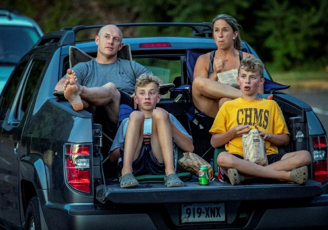 "FILE - In this July 26, 2020, file photo,m Ryan Corvo, left, and his twin brother Alex Corvo, both, 13, and their parents Max Corvo and Kara Jandrew, watch a movie at a coronavirus pandemic ""Pop-up"" drive-in in Berlin, Conn. Connecticut"