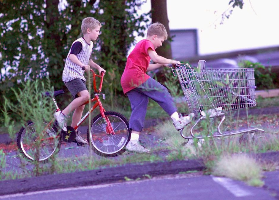 Jesse Moffett, 9 (left) and brother Joseph Moffett, 10 make their way home from a parking lot on Crown Street Sept. 1999. They had been gathering wood for their parking lot fort and taking other discarded lumber to build a go cart at their house down the street.