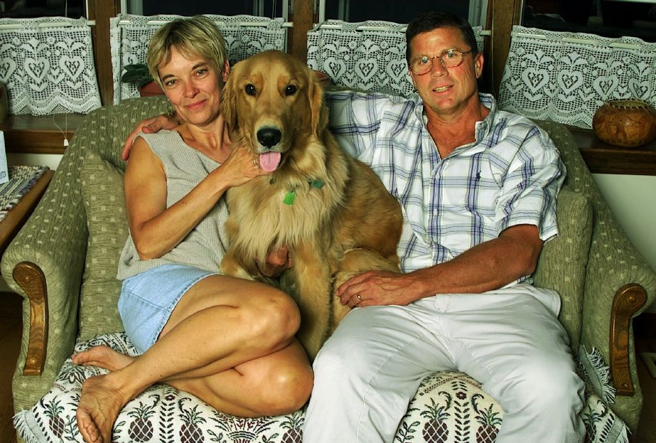"Diane and Rob Szymaszek, with their golden retriever ""Diffley"" relax in their Meriden home Thurs., Sept. 2, 1999."