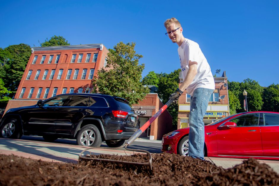 Grady Stephenson, Record-Journal Graphic Artist, rakes mulch in front of the Meriden Y as part of the Record-Journal group taking part in the United Way