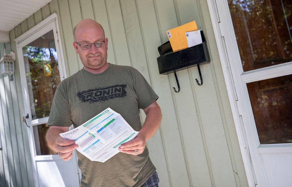 Kevin Casey, of Southington, looks over his electric bill in front of his Visconti Avenue residence, Mon., Jul. 27, 2020. Casey was shocked at the steep spike in the delivery rate from Eversource. Dave Zajac, Record-Journal