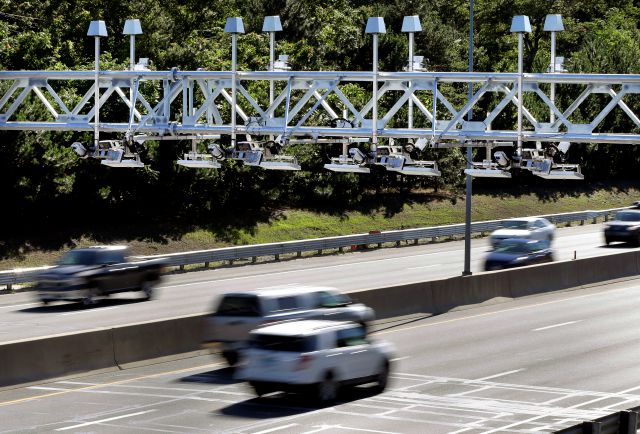 FILE - In this Aug. 22, 2016 file photo, cars pass under toll sensor gantries hanging over the Massachusetts Turnpike in Newton, Mass. Connecticut Gov. Dannel P. Malloy is getting pushback on his plan to spend money on a study of electronic highway tolls in his state. Republican state legislators have balked at the idea, and Democratic State comptroller Kevin Lembo said he will vote against funding the study during a planned vote by the State Bond Commission, scheduled for Wednesday, July 25, 2018. (AP Photo/Elise Amendola, File)