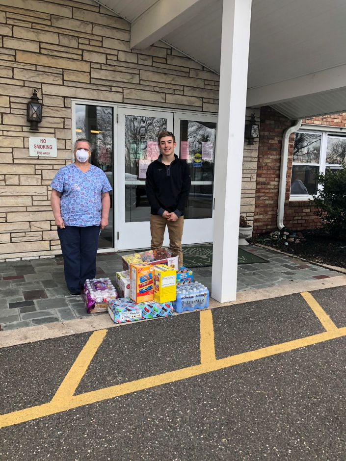 "Mitchell Wollen poses with snacks donated to Skyview Center in Wallingford. Wollen's family has been selling heart shaped signs saying ""thank you"" to healthcare professionals and using the funds to buy snacks for hospital and nursing home staff. 