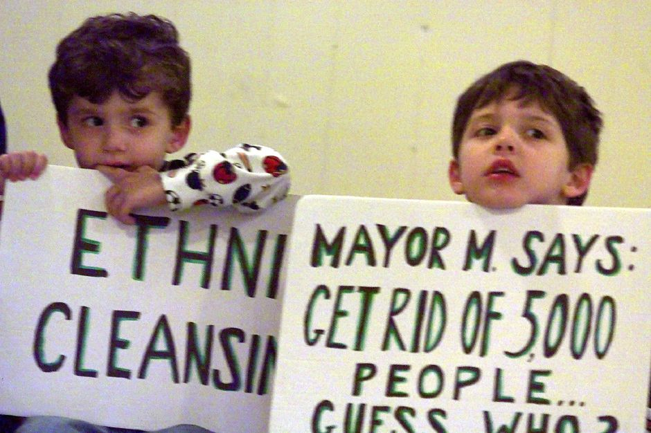 Cristian Coria (left) ,5 and his brother Raul Coria, Jr.,3, hold up protest signs during a resident meeting before protesters marched with lit candles to city hall Monday evening Oct. 25, 1999.