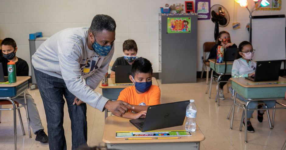 Student teacher Jason Hayes assists student Erik Garcia, 9, in a fourth-grade classroom at Casimir Pulaski Elementary School in Meriden on Thursday.