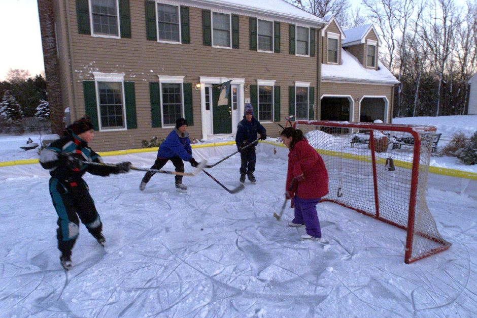 Greg Cohen, left, Jonathan Schanke, Nikolas Cohen, and sister Amy Cohen, right, all play hockey together in the front yard of the Schanke residence in Wallingford. Jonathan Schanke plays hockey with the Connecticut Wolves. They made a skating large skating rink in their front yard Jan. 9, 2001.