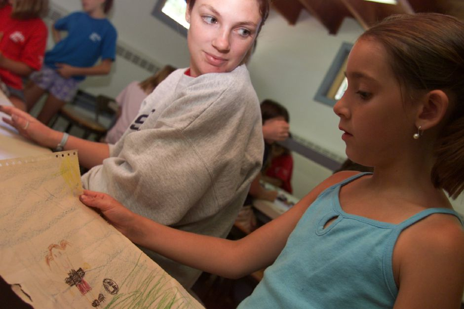 "Sarah Motta, 8, asks the Art Director at Girls Inc. in Meriden, Liz Pavlick, her opinion of her drawing. The girls were also making sports bookmarks using stamps for their ""All Sports"" theme this week, July 2001."