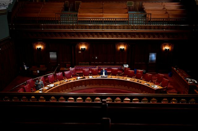 State Sen. Kevin Wilkos, R-Canton, center, listens as State Sen. Rob Sampson, R-Wolcott, left, speaks in an nearly empty senate chamber during special session at the State Capitol, Tuesday, July 28, 2020, in Hartford, Conn. (AP Photo/Jessica Hill)