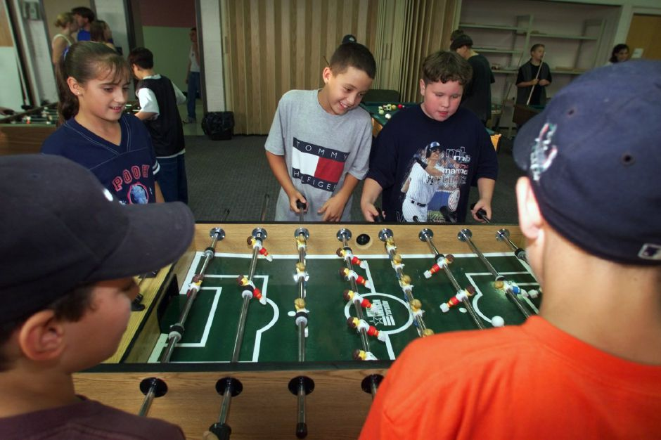 Brittney Perry, 12, left, watches Richard MacLennan, 11, center, and Jin Michonski, 11, play Foosball at the teen center at Holy Angels Community Center Fri., Sept. 10 1999.
