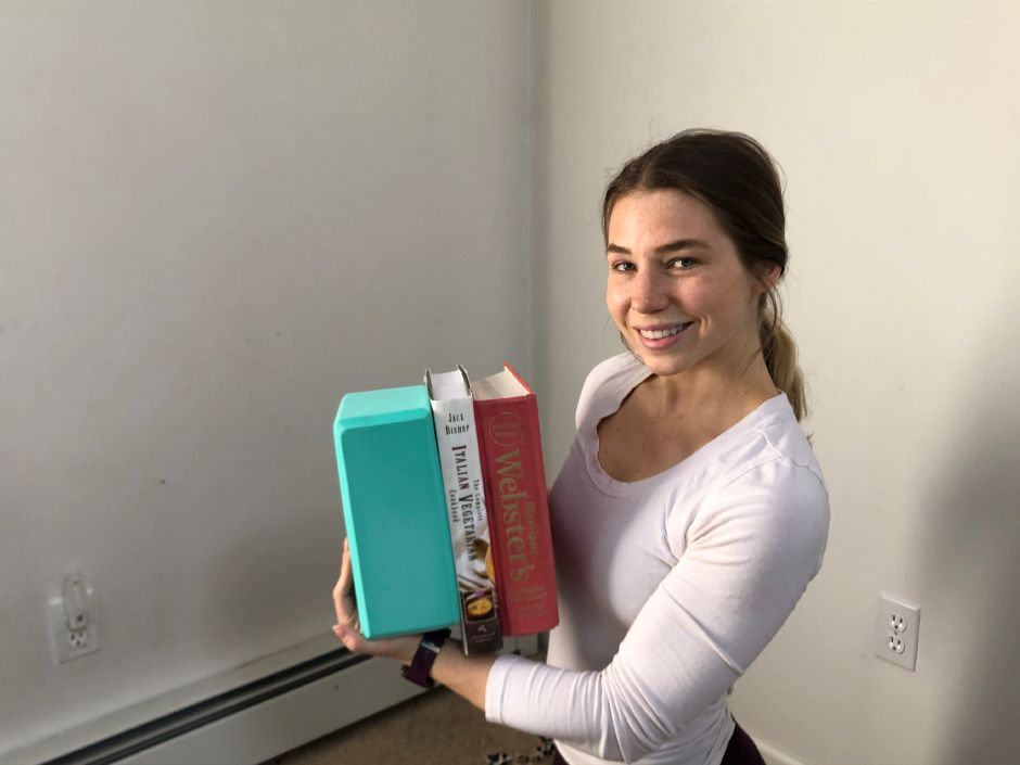 Kristen Dearborn demonstrates how books can be substituted for yoga blocks.