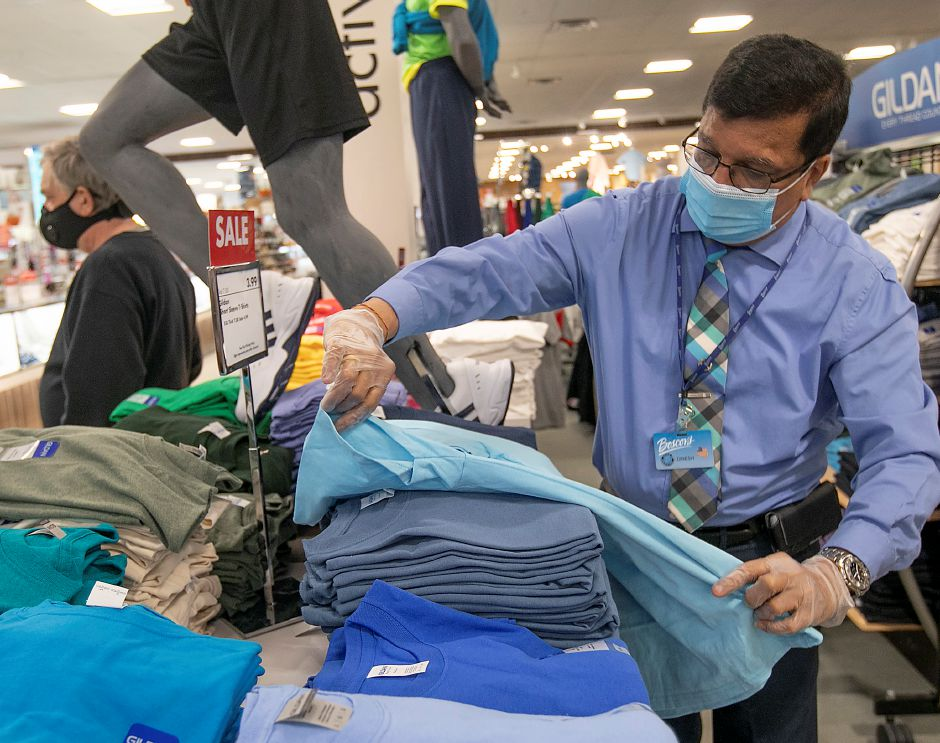 Sales Associate Dinesh Patel folds apparel in the mens sportswear section at Boscov's at the Westfield Meriden mall, Thurs., May 21, 2020. Boscov's department store reopened at 11 a.m. with reduced hours and new safety precautions. Dave Zajac, Record-Journal