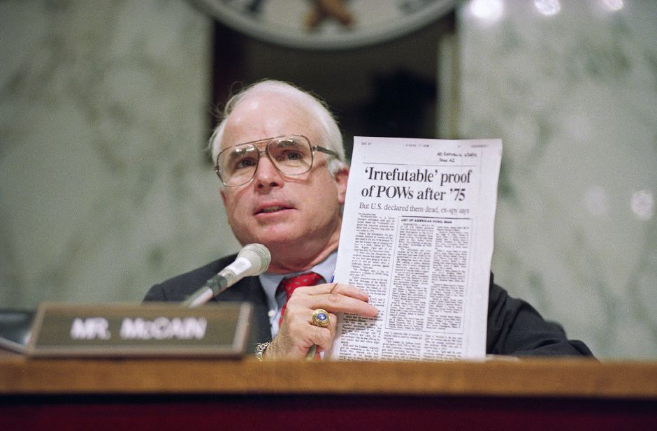** FILE ** In this June 24, 1992 file photo, Sen. John McCain, R-Ariz., holds up an article from the Washington Times on Capitol Hill during a hearing of the Senate Select Committee on POW/MIA Affairs. In 1990s, McCain shouldered the wrenching issue, the long effort to account for American soldiers still missing from the war and to normalize relations with Vietnam. (AP Photo/John Duricka, File)
