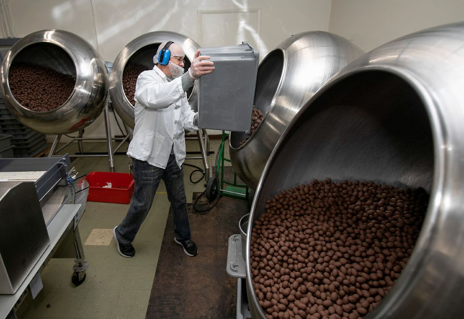 Manuel Delacruz adds a batch of chocolate eggs to a panning machine which smooths over the edges at Thompson Chocolate, 80 S. Vine St., Meriden, Tues., Feb. 4, 2020. Thompson Chocolate is one of 18 stops on the Connecticut Chocolate Trail. Dave Zajac, Record-Journal