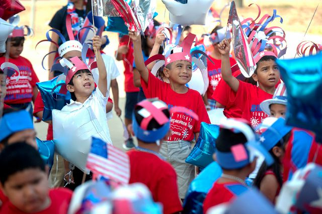 Brooks-Quinn Jones Elementary School students wave flags over their heads as they prepare to march in the school