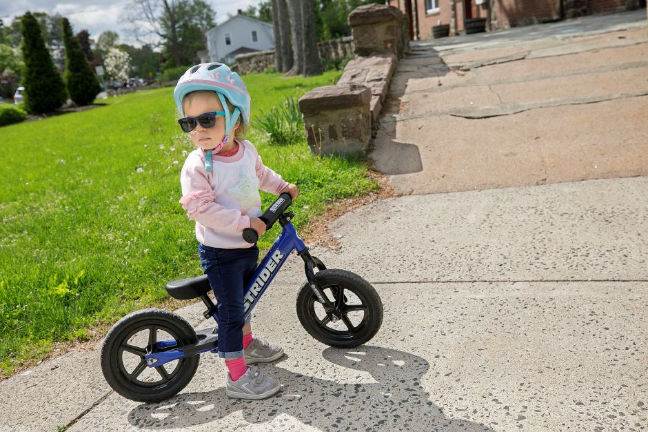 Marina Riddle, 2, of Meriden, pauses on her pedal-less balance bike on Tuesday while she was with her father Marcus at Washington Park in Meriden. Balance bikes teach kids to balance on two wheels and ride independently. Photos by Dave Zajac, Record-Journal