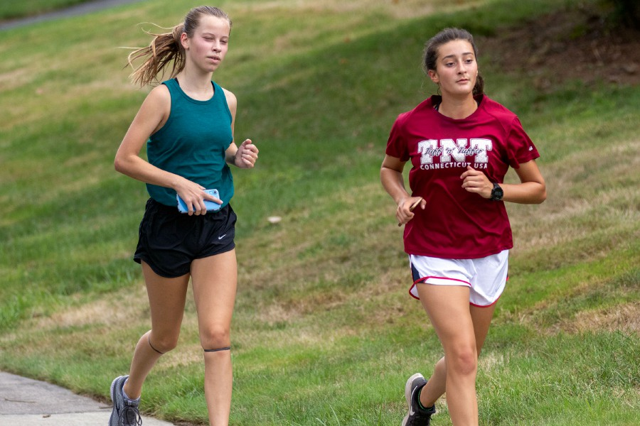 Emma Tommell, left, and Emily Chase of Lyman Hall jog down Bayberry Drive before heading up the hill on Ward Street Extension in Wallingford as part of a training run on Tuesday. Area cross country runners are now training in cohorts for a season scheduled to begin Oct. 1 if the state's COVID-19 case numbers remain stable. Aaron Flaum, Record-Journal
