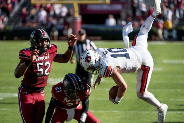 Auburn quarterback Bo Nix (10) is knocked out of bounds by South Carolina defensive back Shilo Sanders (21) and Kingsley Enagbare (52) during the second half of Saturday's game in Columbia, S.C.
