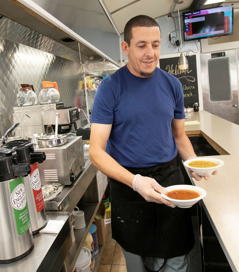 Cook Toumi Abdeslam carries a bowl of ham and bacon tomato soup, left, and chicken noodle soup, right, at The Landmark diner at 82 W. Main St., Meriden, Tues., Oct. 15, 2019. Dave Zajac, Record-Journal