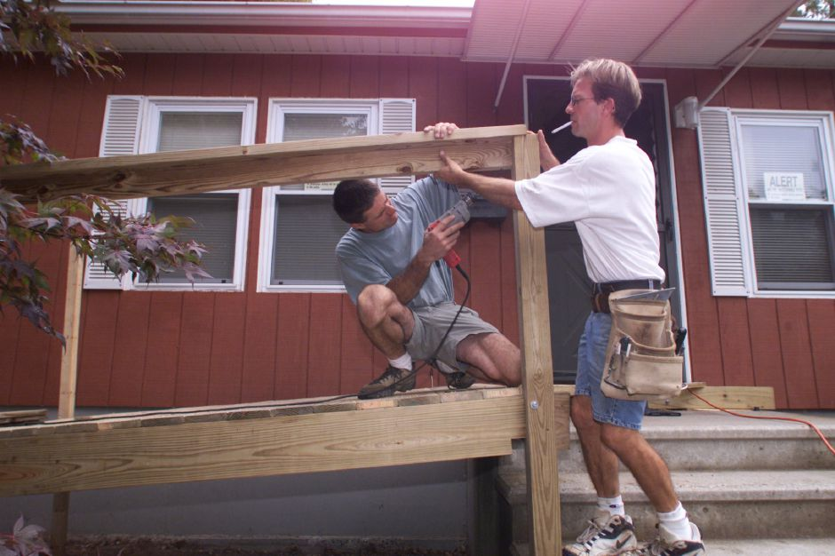 Gianni J. Morasutti, left, project manager at Ramps and Rails LLC and Ron Wagner, an employee, work together building a residential access ramp at a Meriden house Friday Sept. 1999. They are working together at constructing a handicap accessable ramp.