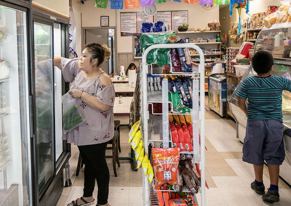 Georgina Ponce, co-owner of La Poblanita Grocery & Deli in Meriden, tends to vegetables in a refrigerator at the 39 Colony St. business, Thurs., Aug. 15, 2019. La Poblanita Grocery & Deli recently started to build a dining area in vacant space next door at 41 Colony St. Dave Zajac, Record-Journal