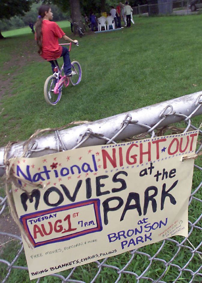 A makeshift marquee is attached to the front fence of Bronson Park as Christina Rodriguez, 12 of Meriden wheels her bike into the park to see Tuesday night