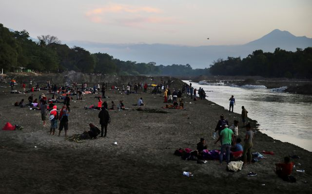 Central American migrants camp on the Mexican shore of the Suchiate River on the border with Guatemala near the Tacana volcano, near Ciudad Hidalgo, Mexico, at sunrise, Tuesday, Jan. 21, 2020. Hundreds of Central American migrants were stranded in a sort of no-man's land on the river border between Guatemala and Mexico after running up against lines of Mexican National Guard troops on Monday deployed to keep them from moving en masse into the country and on north toward the U.S. (AP...